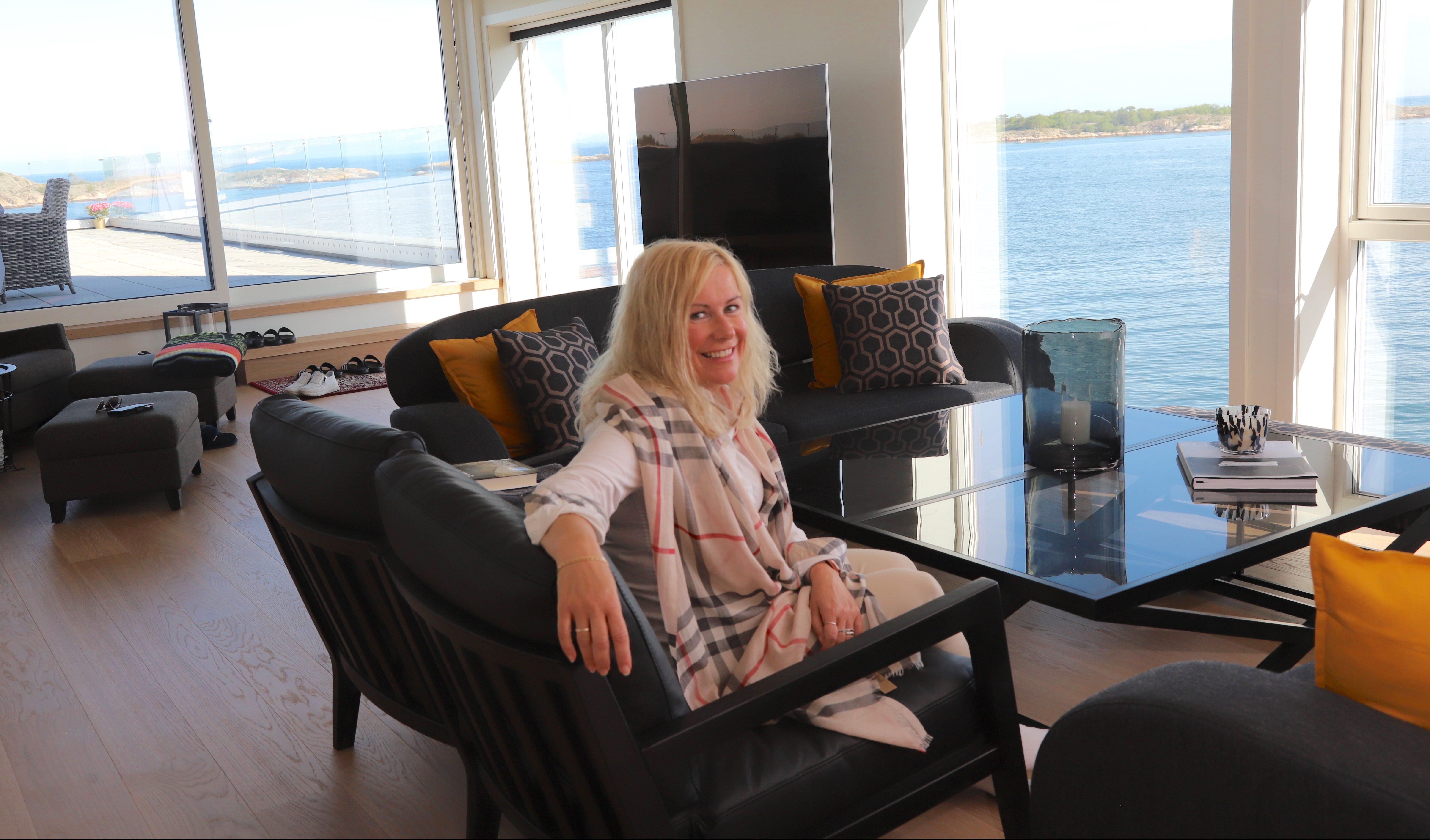 Cesilie koser i stua si med utsikt over fjorden